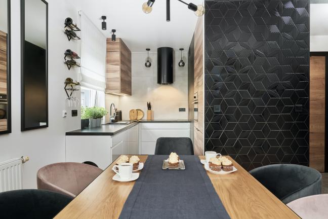Mała kuchnia otwarta na nowoczesną jadalnię w drewnie — projekt wrocławskiego mieszkania