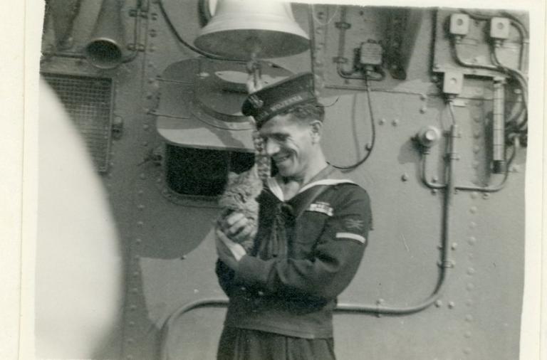 Zdjęcie czarno-białe marynarza z kotem na statku