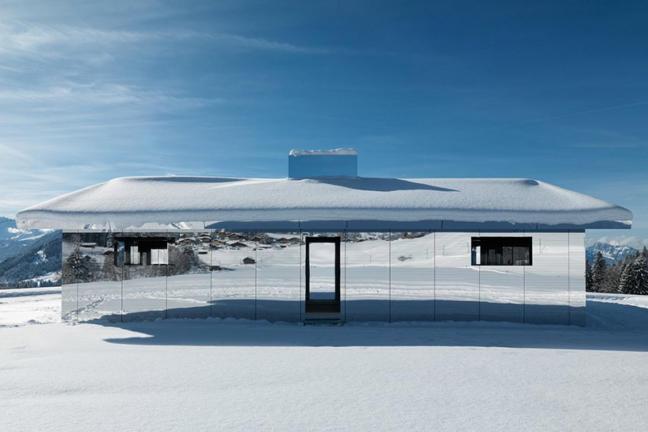 Lustrzany dom w zimowej scenerii