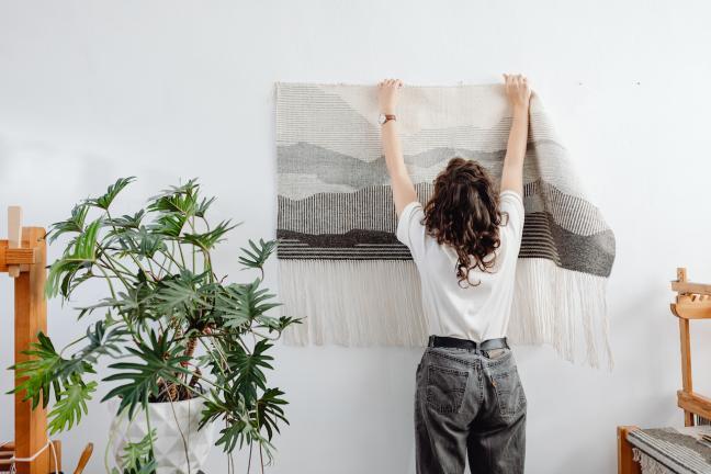 Kilim wieszany przez kobietę na ścianie marki Tartaruga